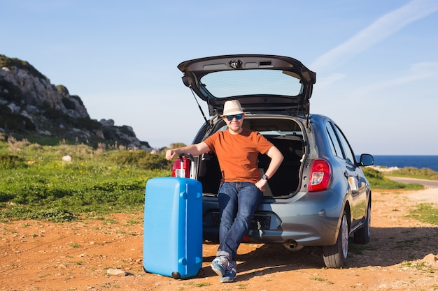 Homem engraçado e feliz passando as férias de verão. conceito de viagens de carro.