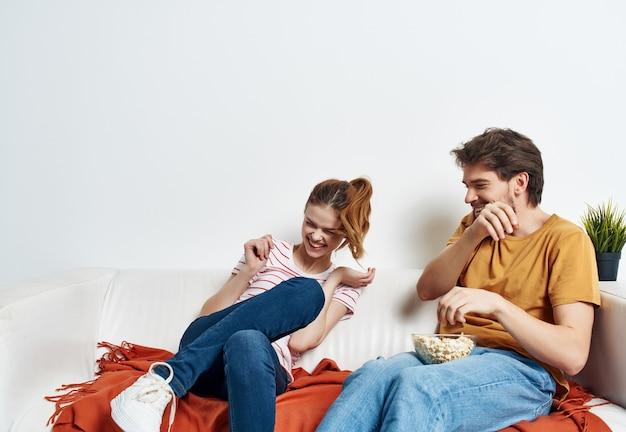Homem engraçado e mulher em casa no sofá divertido resto pipoca
