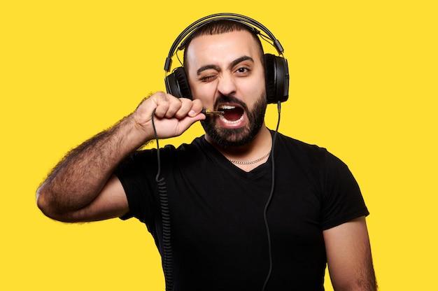 Homem engraçado e positivo com uma barba em fones de ouvido ouve música e morde o fio amarelo. dia internacional do dj