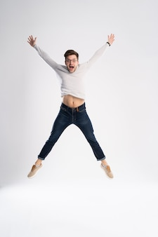 Homem engraçado em camiseta casual e jeans pulando isolado sobre fundo branco