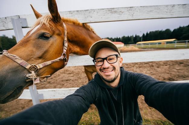 Homem engraçado em copos tomando selfie com cabeça de cavalo atrás dele.