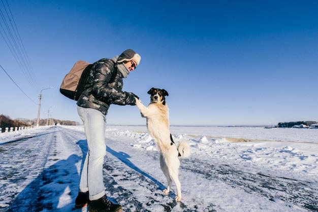 Homem engraçado em roupas de inverno, segurando as patas de cachorro sem teto em dia frio de inverno na natureza.