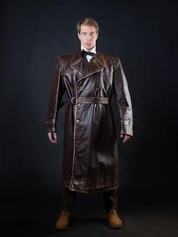 Homem engraçado em um casaco de couro ridículo, roupas estilo vintage, foto em um fundo preto, um personagem brincalhão faz caretas estúpidas
