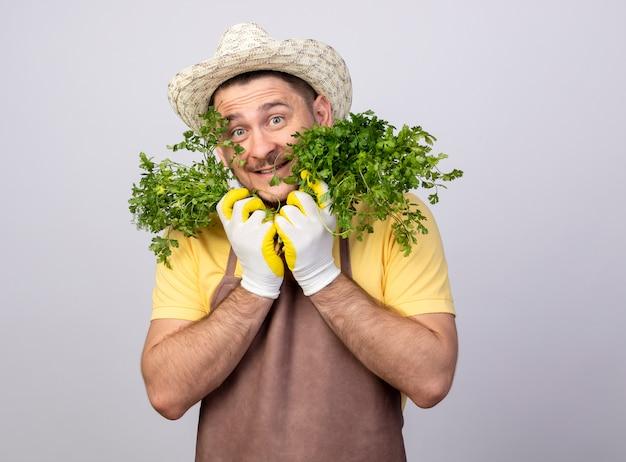 Homem engraçado jovem jardineiro vestindo macacão e chapéu em luvas de trabalho segurando ervas frescas, olhando para a frente, sorrindo com uma cara feliz em pé sobre a parede branca