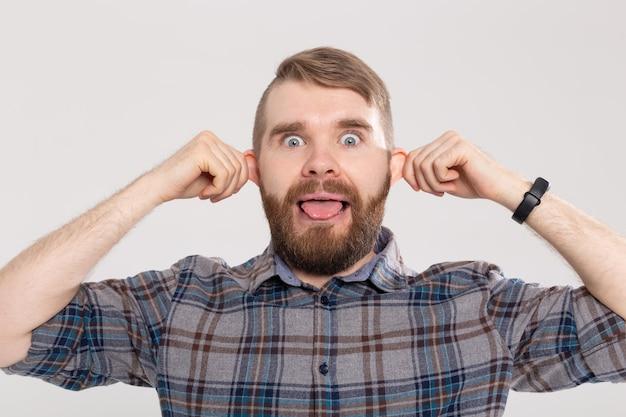 Homem engraçado, louco, brincalhão e bonito com camisa xadrez, fazendo cara de macaco bobo com orelhas salientes mostrando a língua
