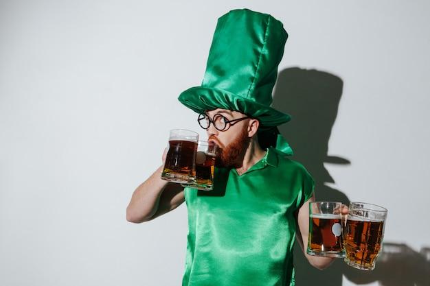 Homem engraçado no traje de st.patriks, bebendo cerveja de dois copos