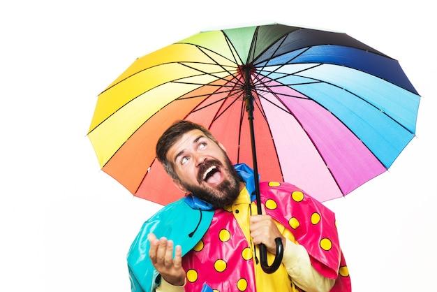 Homem engraçado outono com capa de chuva sob o guarda-chuva está tentando ver se há chuva.