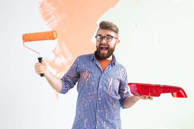 Homem engraçado, pintando a parede interior com rolo de pintura na casa nova. cara com rolo aplicando tinta em um