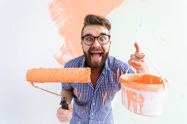 Homem engraçado pintando a parede interior da casa nova. redecoração, renovação, reparação de apartamentos.