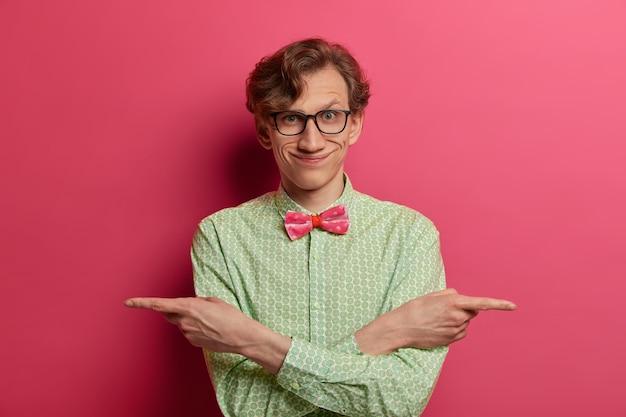 Homem engraçado positivo aponta as mãos de lado com os braços cruzados sobre o peito, dá variantes, escolhe entre duas opções, indica direita e esquerda, veste camisa verde elegante com gravata borboleta, óculos