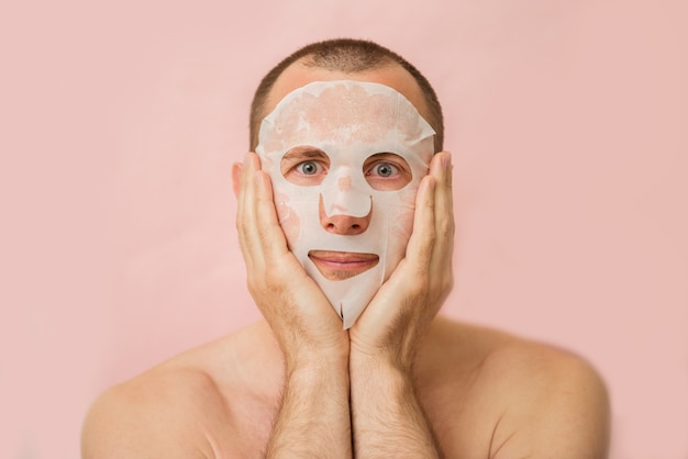 Homem engraçado recebendo máscara facial nutritiva