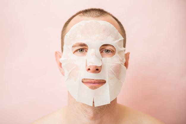 Homem engraçado recebendo máscara facial nutritiva.