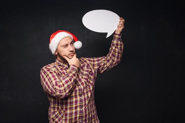 Homem engraçado sério no chapéu de papai noel de natal vermelho contém papelão branco vazio como em branco ou simulado com espaço de cópia para o texto. fundo preto