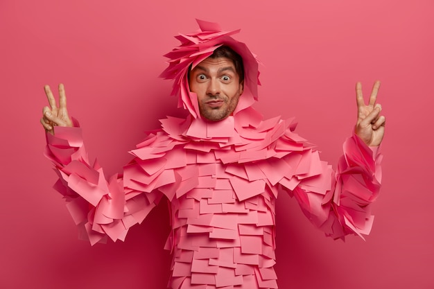 Homem engraçado surpreso se diverte no escritório, posa em traje criativo feito de notas adesivas, levanta os dedos em gesto de vitória, mostra o símbolo da paz, isolado sobre a parede rosa. roupa de papel. monocromático