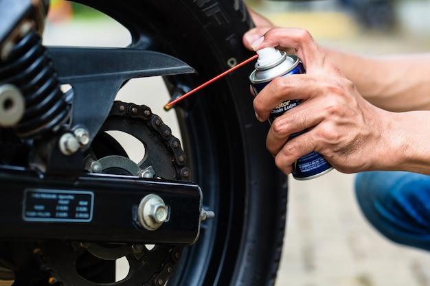 Homem engraxando corrente de motocicleta, close-up disponível
