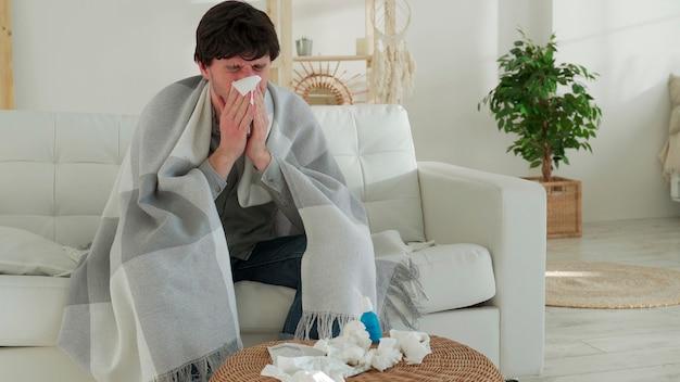 Homem enrolado em um cobertor sente-se doente com resfriado e febre em casa doente com gripe sentado no sofá