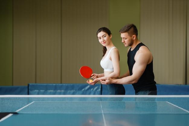 Homem ensina mulher a jogar pingue-pongue, treinando dentro de casa.