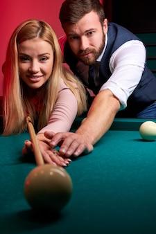 Homem ensinando a namorada a jogar sinuca, mostrando a ela como mirar a bola na mesa de bilhar