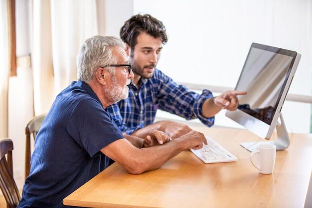 Homem ensinando homem idoso a usar o computador