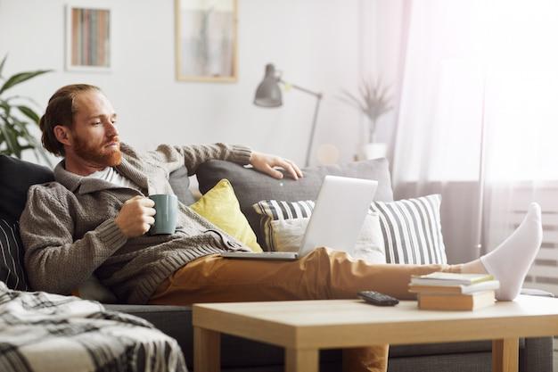 Homem entediado assistindo vídeos via laptop
