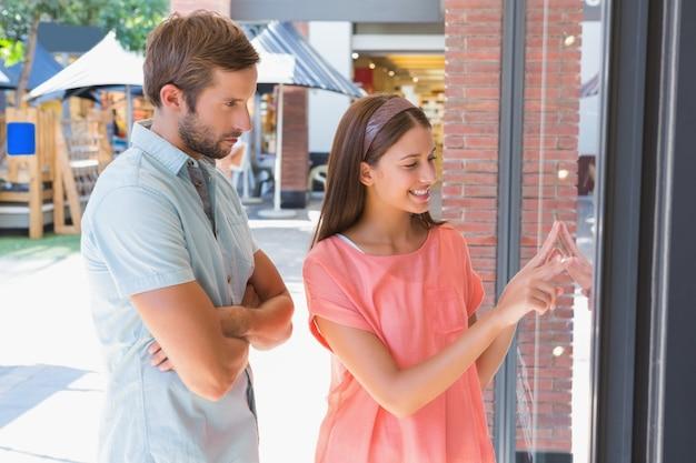 Homem entediado observando sua esposa feliz olhando uma janela