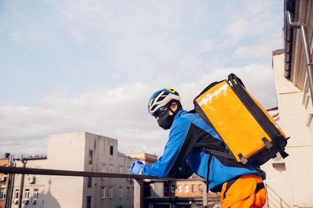 Homem entrega comida e sacolas de compras durante o isolamento