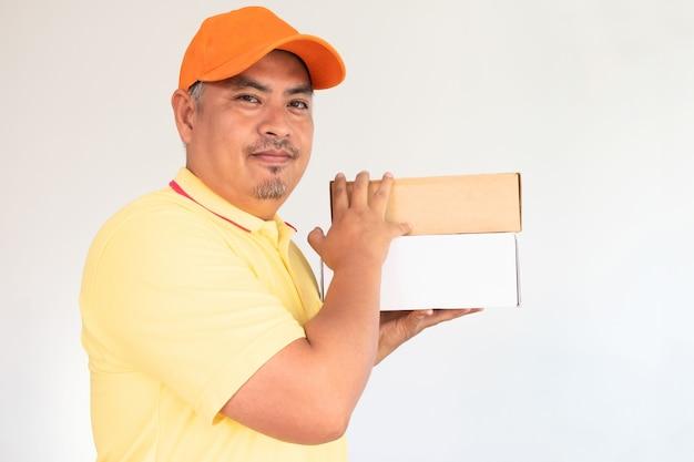 Homem entrega, em, laranja, boné, e, camisa amarela, carregando, caixa postal postal, enviando, para, destinatário