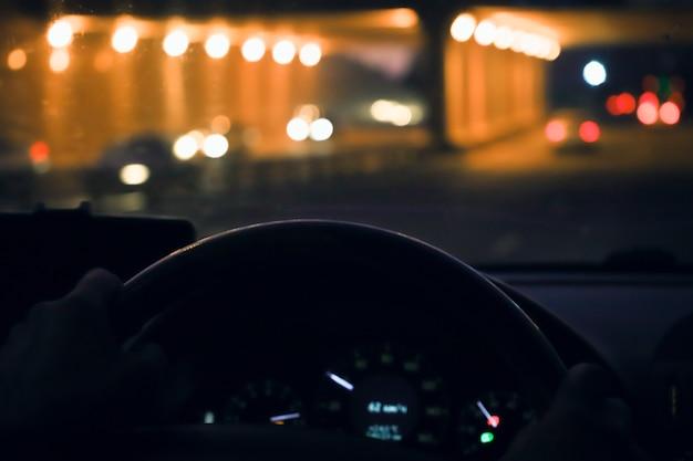 Homem entrega o motorista no volante de um carro moderno com o painel do carro e o fundo da cidade à noite