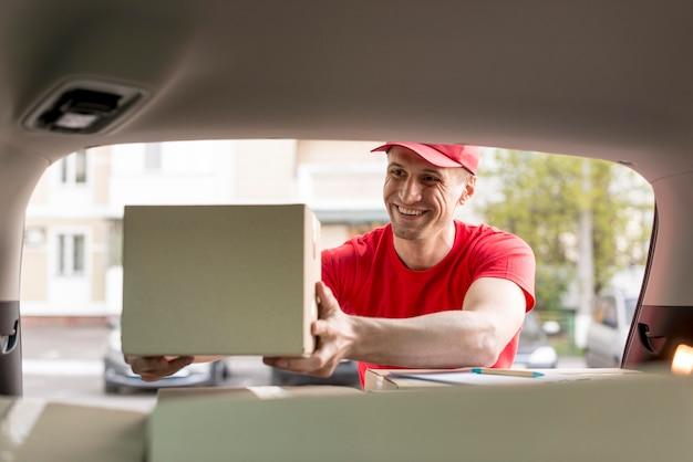 Homem entrega sorridente trabalhando