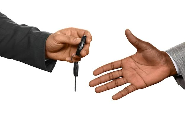 Homem entregando as chaves do carro. confie em mim. perto do luxo. movendo-se com conforto.