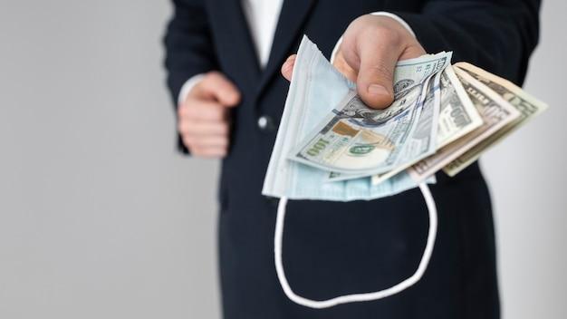 Homem entregando um monte de notas de dólar com uma máscara médica