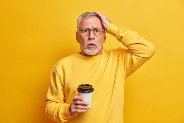 Homem envelhecido barbudo e envergonhado mantém a mão na cabeça e olha estupefato para a frente, bebe café para viagem vestido com um macacão casual isolado sobre a parede amarela não posso acreditar no fracasso