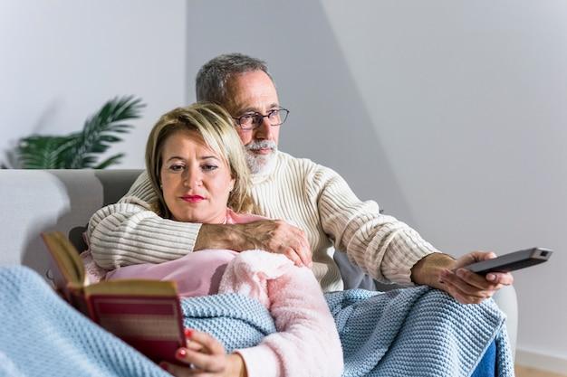 Homem envelhecido, com, controle remoto tv, observar, tv, e, leitura mulher, livro, ligado, sofá