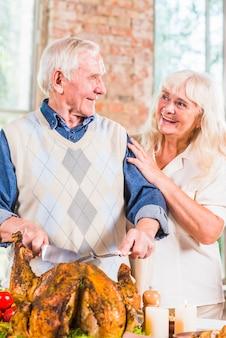 Homem envelhecido corte frango assado na mesa perto de mulher