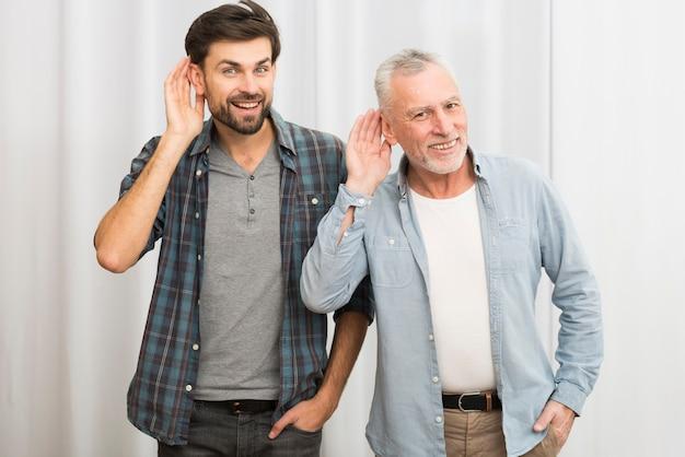 Homem envelhecido e jovem feliz com as mãos perto das orelhas