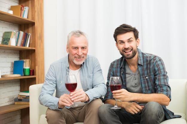 Homem envelhecido e jovem sorridente com copos de vinho no sofá