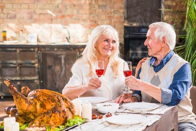 Homem envelhecido e mulher com óculos perto de frango assado