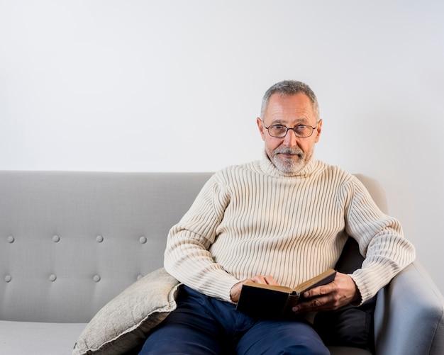 Homem envelhecido lendo com óculos