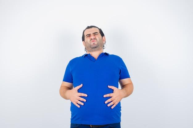 Homem envelhecido médio em t-shirt azul, segurando as mãos na barriga e parecendo indisposto, vista frontal.