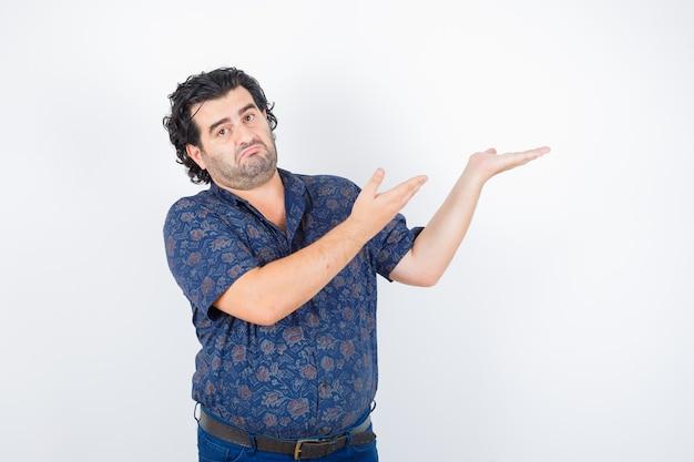 Homem envelhecido médio na camisa, mostrando algo e parecendo hesitante, vista frontal.
