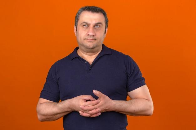 Homem envelhecido médio pensativo, vestindo camisa polo, olhando para cima e pensando sobre parede laranja isolada