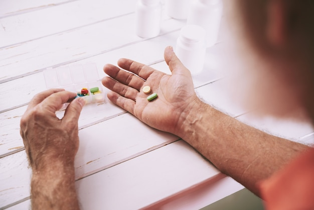 Homem envelhecido tomando analgésicos