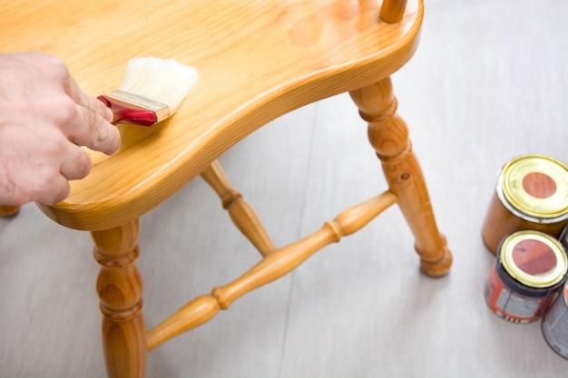 Homem envernizando uma cadeira de madeira