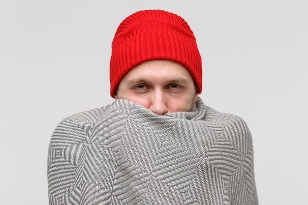 Homem envolto em manta de malha bege quente, sofrendo de frio
