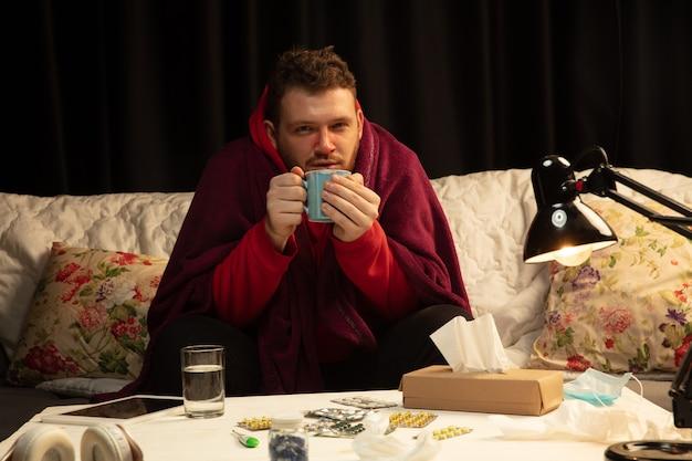 Homem envolto em uma manta parece doente, espirrando e tossindo, sentado em casa dentro de casa