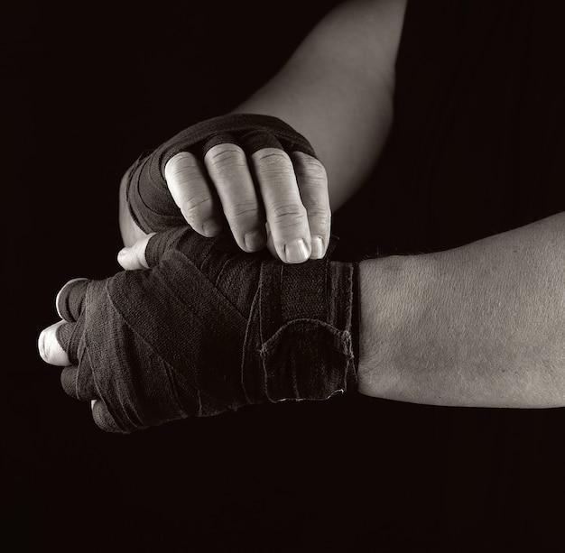 Homem envolve as mãos em bandagem têxtil preta para esportes