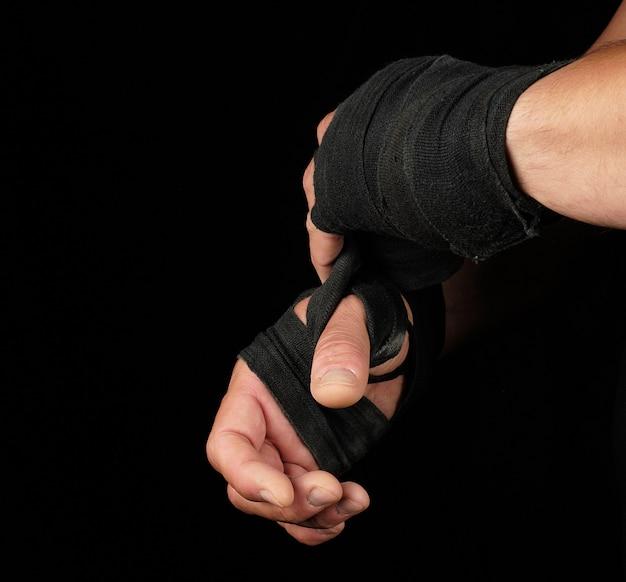 Homem envolve as mãos em bandagem têxtil preto para esportes