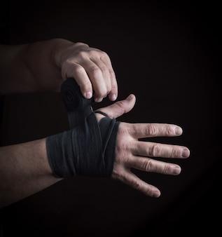 Homem envolve as mãos em bandagem têxtil preto