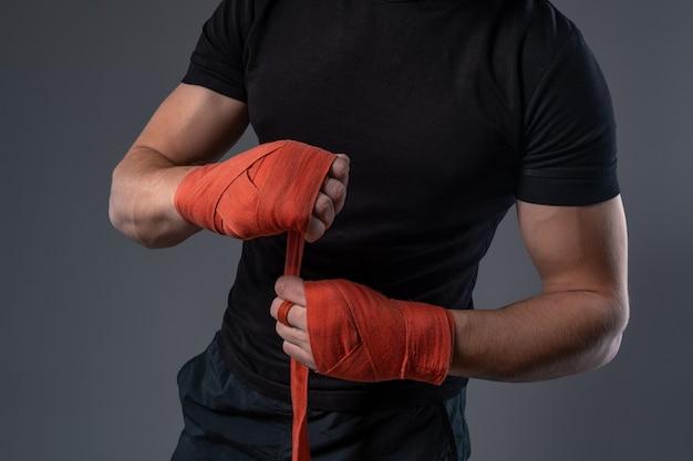 Homem envolvendo as mãos com fita vermelha se preparando para o boxe