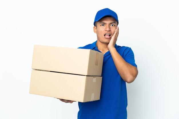 Homem equatoriano de entrega isolado no fundo branco com expressão facial de surpresa e choque